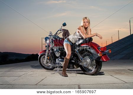 Young sexy blonde sitting on her motorcycle on the background of a summer sunset