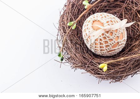 Easter egg in handmade knitted bag in brown nest with spring decor. Selective focus.