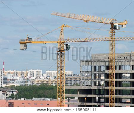 Two yellow hoisting tower cranes construction buildings and residential houses