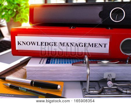 Red Ring Binder with Inscription Knowledge Management on Background of Working Table with Office Supplies and Laptop. Knowledge Management Business Concept on Blurred Background. 3D Rendering.