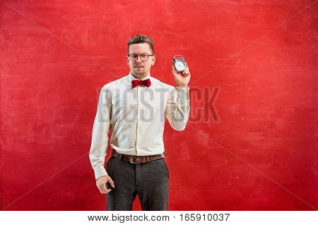 The young funny man with abstract clock on red studio background. concept - time to congratulate