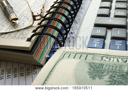 Note with data, calculator and cash. Financial accounting concept.