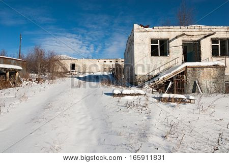 Abandoned prison settlement with decayed buildings in Northern Kolyma winter view