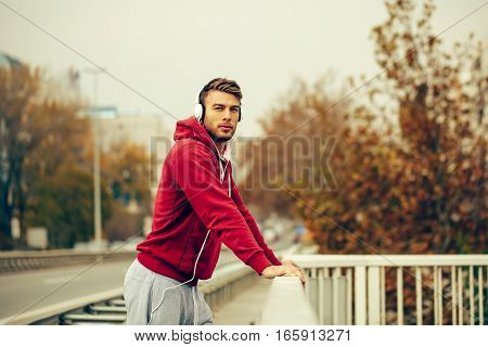 Man resting on the bridge after running and listening to music through headphones