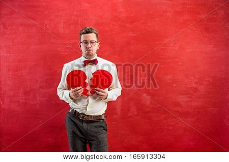 The young funny man with abstract broken heart on red studio background. Concept - unhappy love