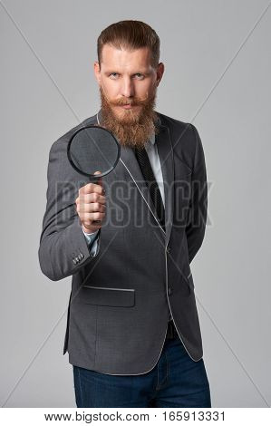 Serious hipster business man with beard and mustashes in suit holding magnifying glass, over grey background