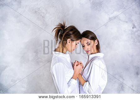 Two young brunette sisters in white shirts holding hands