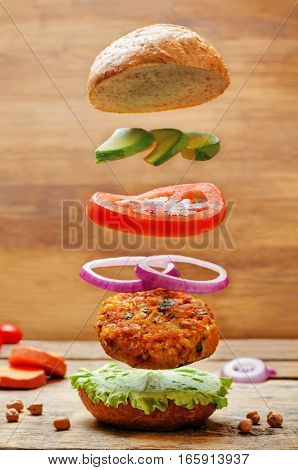 Flying vegan sweet potato chickpea burgers on wood background