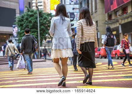 Hong Kong, China - December 6, 2016: Causeway Bay is one of best place for shopping, always full of tourists and business people. Asian couple male collegues crossing the Times Square intersection.