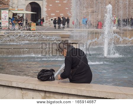 Milan, Italy, 03-21-2014. An elderly woman collects coins in the fountain in front of the castle and then counts them.