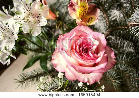 Bouquet of yellow-pink rose with Alstroemerias and silver fir twigs on light wooden table