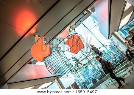 Hong Kong, China - December 4, 2016: two red Apple logos and customers looking the new technological products and shop clerks in red. Apple store, IFC Mall, with Central District skyline on background