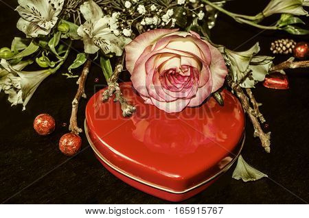 Bouquet from white flowers,rose and dry twigs and red box heart with chocolates on blackplank