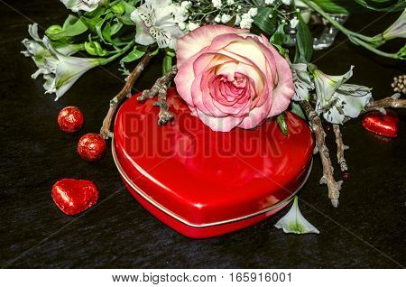 Bouquetofdelicate flowerswith roseon red box with chocolate