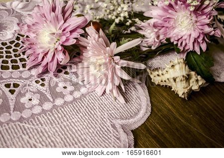 Bouquet of pink asters with sea shell on lacy napkin lying on dark wooden table