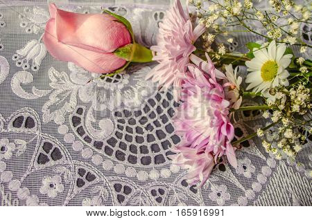 Bouquet of pink and white aster with bud pink rose on lace tablecloth