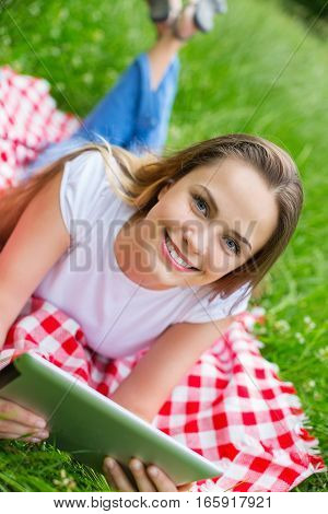 Happy young woman with digital tablet laying on grass