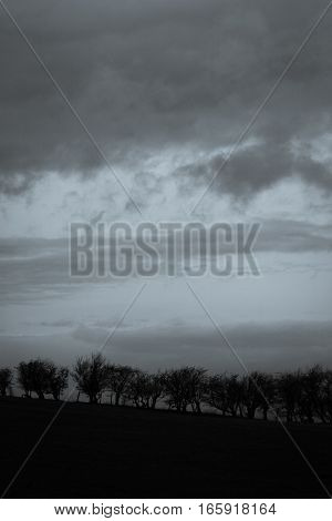 A stormy overcast sky over an early English countryside scene.