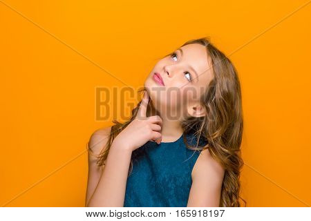The happy teen girl looking up on orange studio background