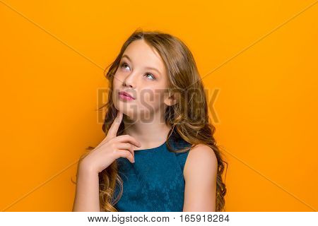The thoughtful teen girl looking up on orange studio background