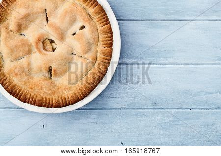 Homemade apple pie dessert shot from overhead over a blue rustic wooden table top with room for copy space.