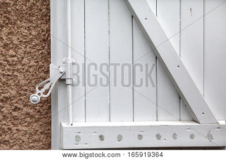 Background: sash wooden window shutters painted in white with a forged iron lock and yellow-pink wall