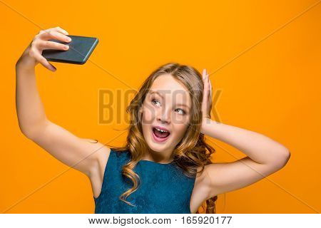 The face of playful happy teen girl with long hair on orange studio background making photos selfie