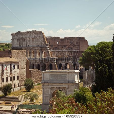 A long view over the ancient Roman Forum ruins with the familiar view of the Colosseum in the distance.