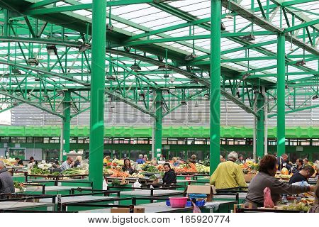 BELGRADE SERBIA - October 24: Busy local green market with people buying fresh fruits and vegetables in Belgrade Serbia - October 24 2016; Market stalls full with piles of fresh organic fruits and vegetables.