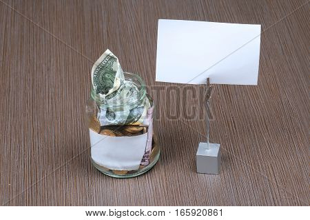 Glass jar full with coins and paper money and blank note