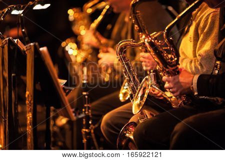 A candid view along the saxophone section of a big band in concert.