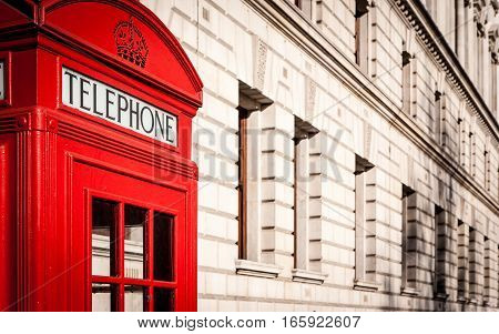 Traditional old-style UK red phone box set against a beige government building in central London.
