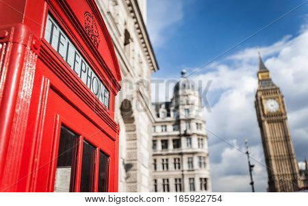Detail of an iconic red British telephone box with Big Ben visible in the background.