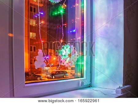 bright colored electric garland in the window in winter night