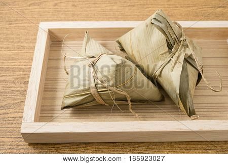 Chinese Cuisine Delicious Zongzi or Sticky Rice Dumpling in A Wooden Tray for Dragon Boat Festival.