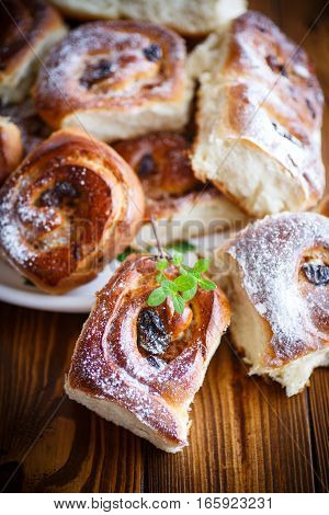 sweet rolls with raisins on the wooden table