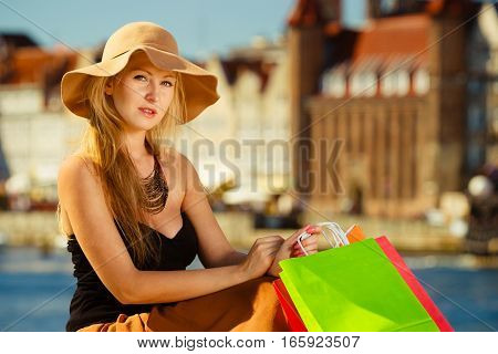 Spending money buying things concept. Fashionable woman resting after big shopping sitting with bags wearing glamorous outfit and big sun hat