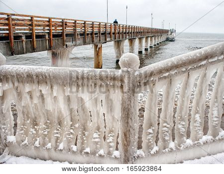 ice covered fence on the beach on cold gloomy winter day