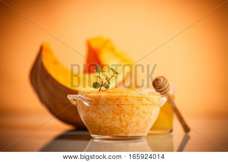 boiled pumpkin with rice and honey on a orange background