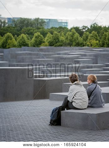 BERLIN GERMANY - JUNE 2 2006: A pair of tourists sit to admire and contemplate over the Holocaust Memorial in Berlin Germany.