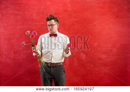 The young funny man with broken bouquet on red studio background. Concept - unhappy love