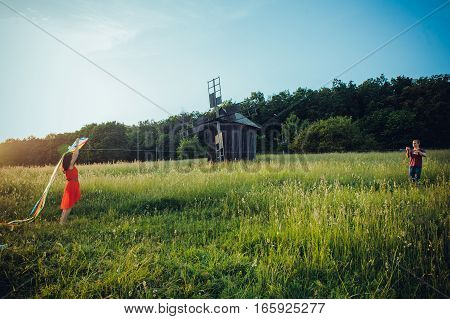 Happy Young Couple In Love Runing A Kite On The Field. Two, Man And Woman Smiling And Resting In The