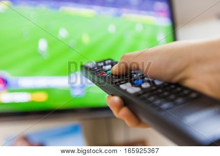 Hand Using a Remote Control with a Television in the Background