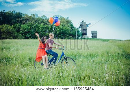 Happy Young Couple Having Fun Outdoors Going For A Ride With The Bicycle In The Countryside