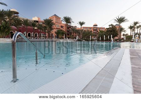 HURGHADA, EGYPT - NOVEMBER 17 2006: An early morning view of a hotel resort swimming pool just as the sun is about to rise and well before any tourists emerge.