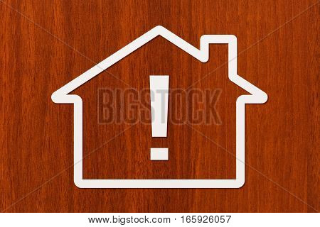 Paper house with exclamation point inside on wooden background. Mortgage housing concept. Abstract conceptual image