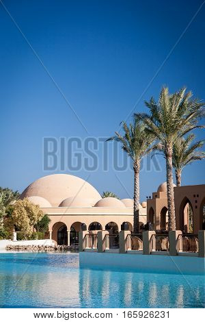 HURGHADA, EGYPT - NOVEMBER 21 2006: A 5-star hotel resort with the pool palm trees and restaurant in view against a cloudless blue sky providing copy space.