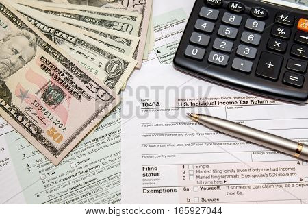 Filing federal taxes for refund - tax form 1040 calculator pen dollar