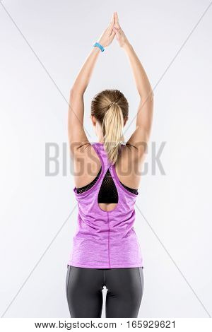 Back view of sporty blonde woman stretching her arms on white