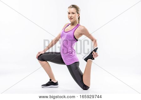 Sporty woman in sportswear stretching legs and looking at camera on white
